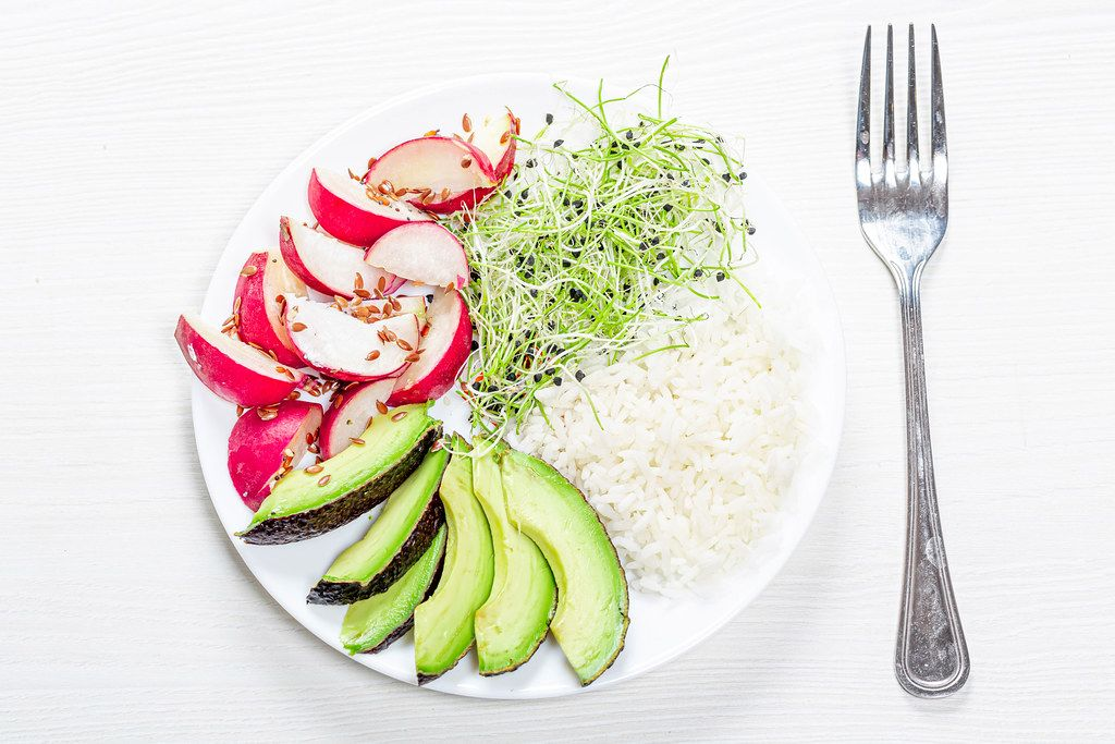 The view from the top rice with slices of radish, avocado and micro-greens onions