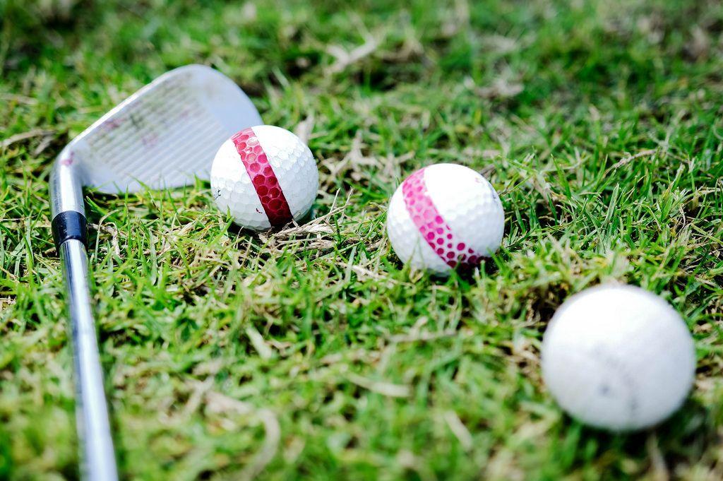Three golf balls and a golf club