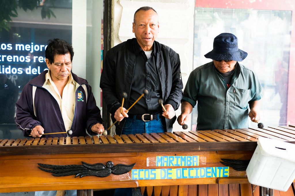 Three men playing the marimba in public