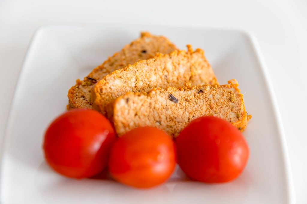 Three red cherry tomatoes in front of vegan Organic Tofu Rosso slices by Taifun, on a white plate