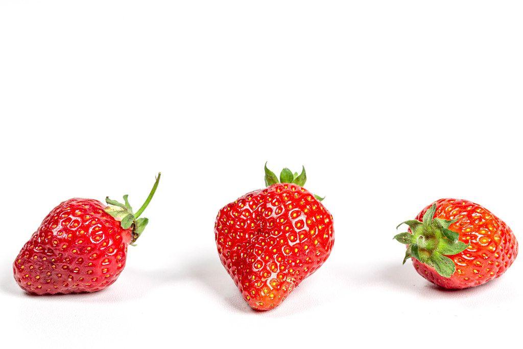 Three ripe strawberries on a white background