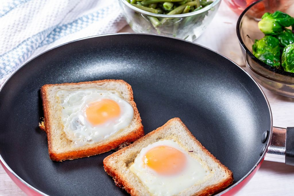 Toast bread with fried eggs in a frying pan
