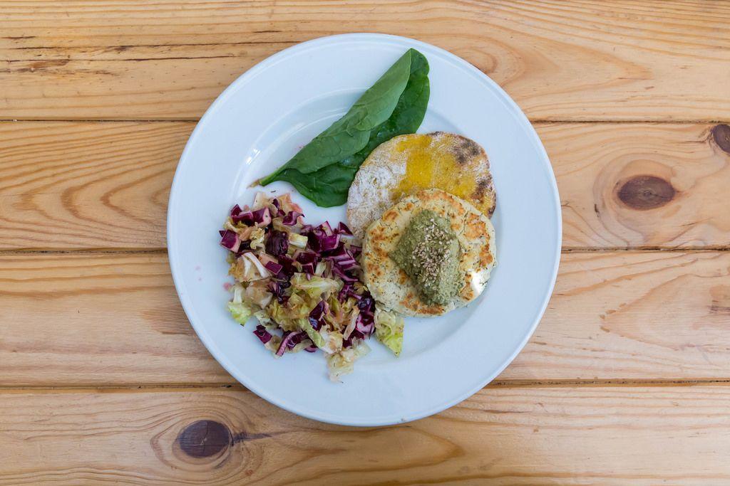 Tofu Burger aus weissen Bohnen serviert mit Salat und Spinat auf Holztisch