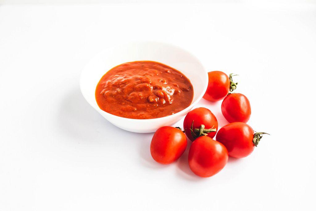 Tomatensoße auf einem Teller mit Tomaten auf weißem Hintergrund