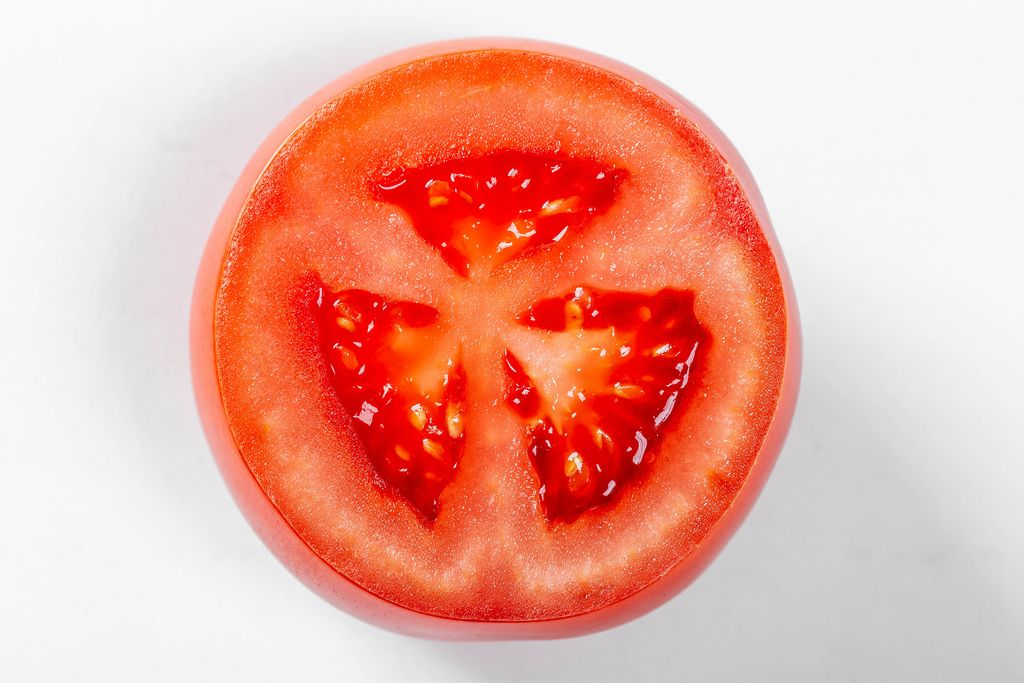 Tomato slice on white background, top view