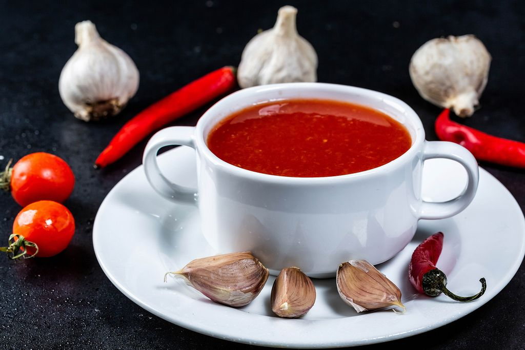 Tomato soup in a tureen on a dark background with garlic, cherry tomatoes and garlic