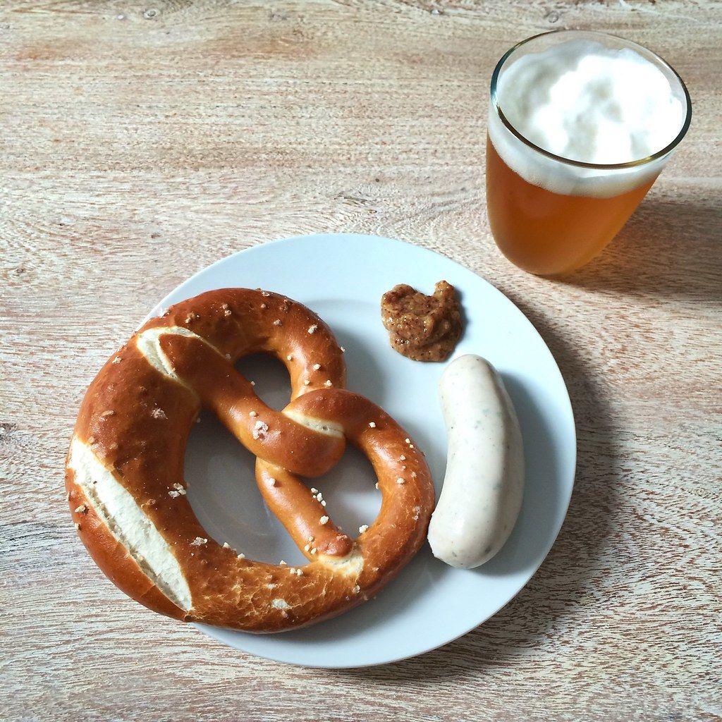 Top vie of typical Bavarian meal: German veal sausage, bretzel and beer