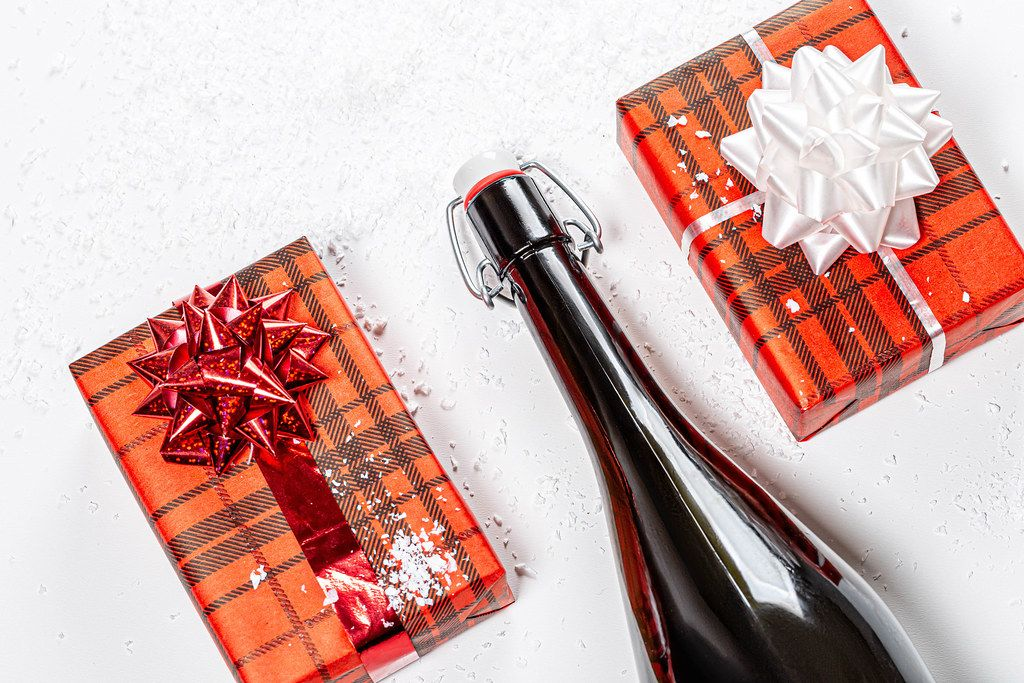 Top view a bottle of champagne and two gift boxes. The concept of Christmas (Flip 2019)