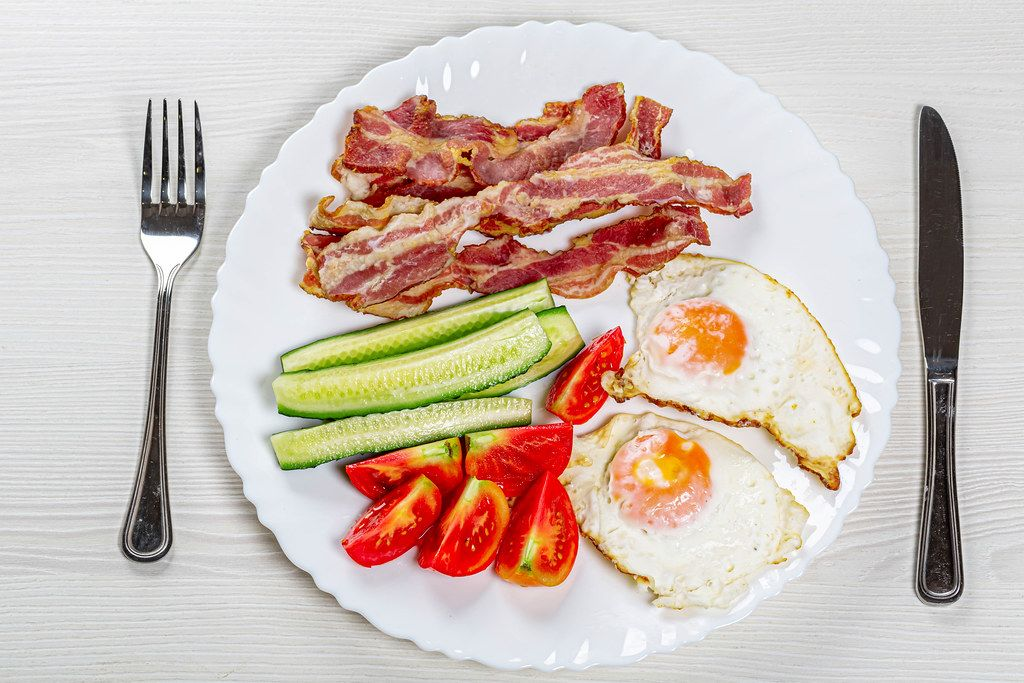 Top view Breakfast with scrambled eggs, bacon and vegetables