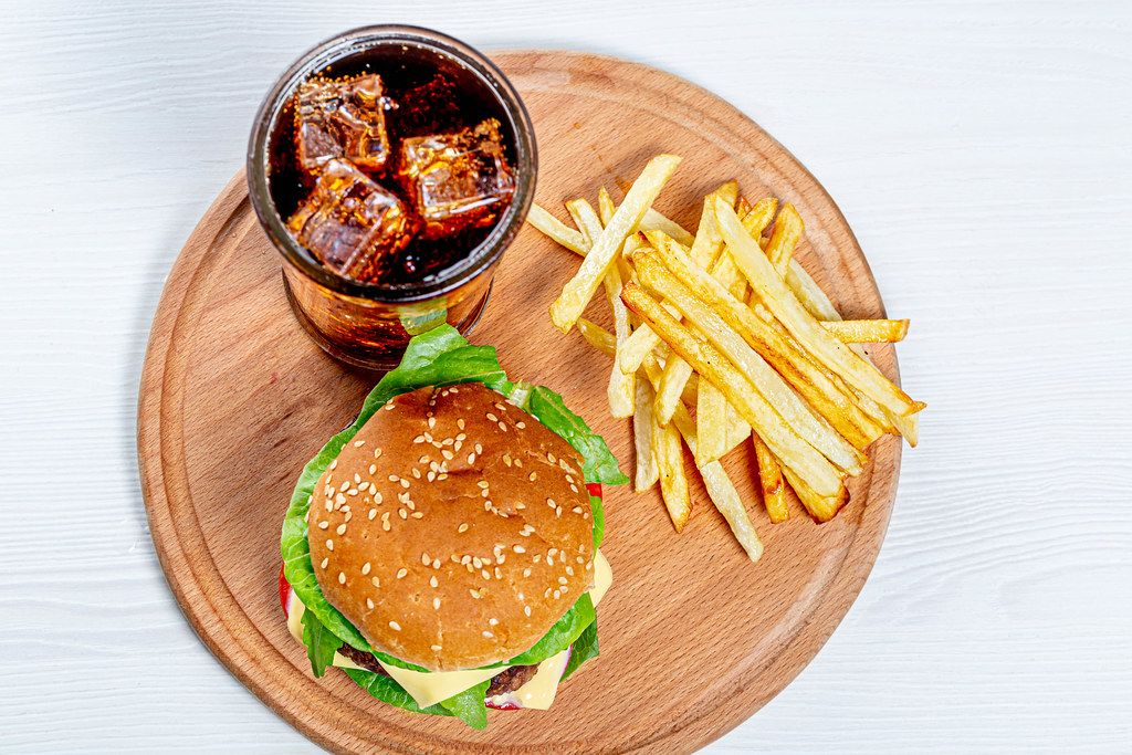 Top view Burger, fries and iced drink on round kitchen Board
