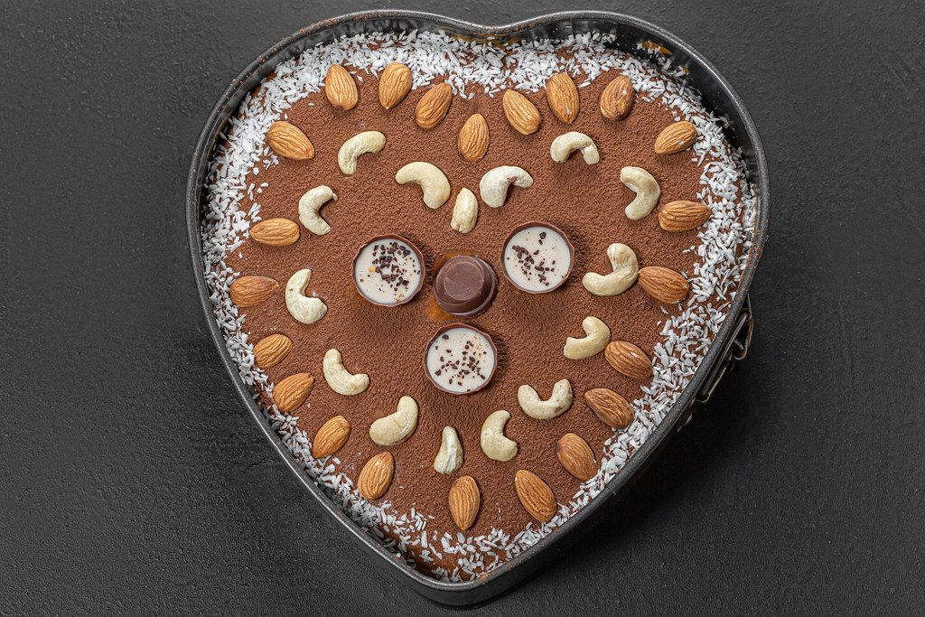 Top view chocolate heart cake with nuts and coconut on black background (Flip 2019)