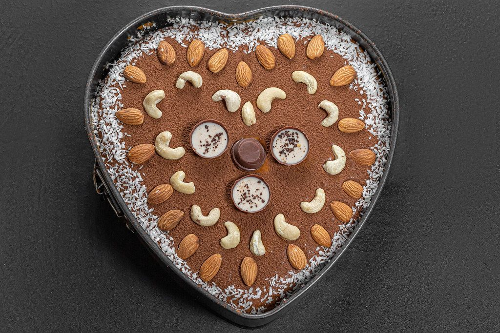 Top view chocolate heart cake with nuts and coconut on black background