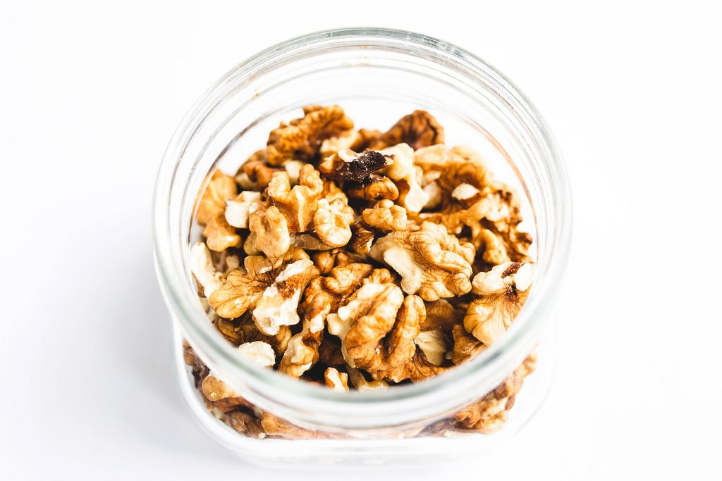 Top view close up of jar of walnuts white background