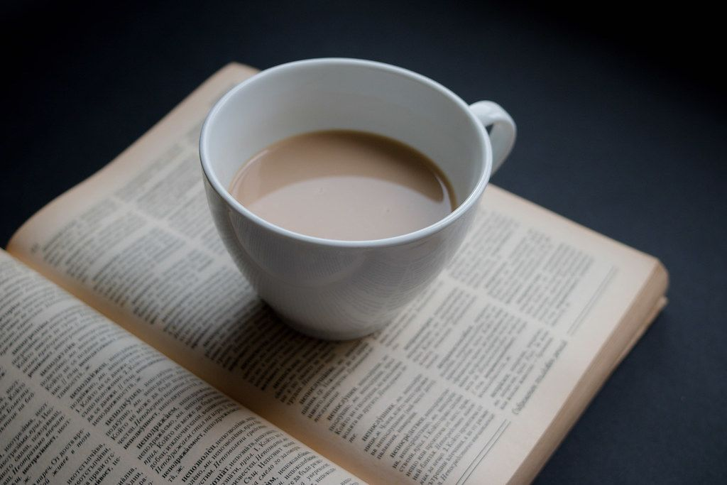 Top View Close Up Photo of Cup of Coffee standing on open Book on Black Table