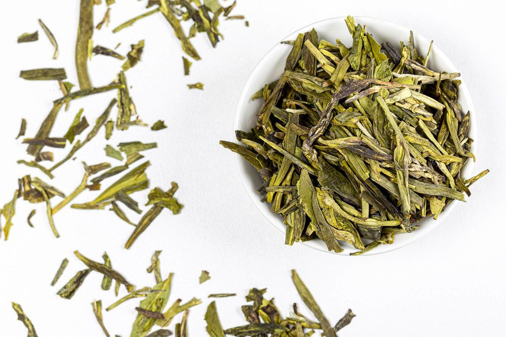 Top view, dried green tea leaves on white background