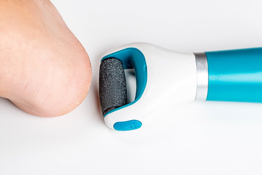 Top view, electric roller file for removing coarse skin of the heel and a woman's leg