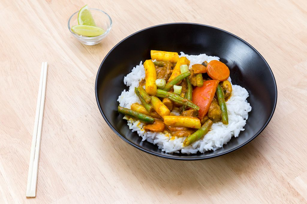 Top View Food Photo of Vegetarian Thai Curry with Rice in Black Ceramic Bowl next to Chopsticks and Small Glass Bowl with Lemon on Wooden Table
