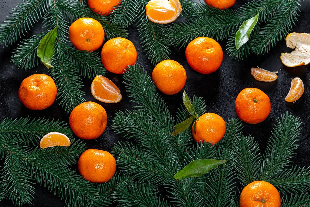 Top view fresh tangerines with Christmas tree branches on black background