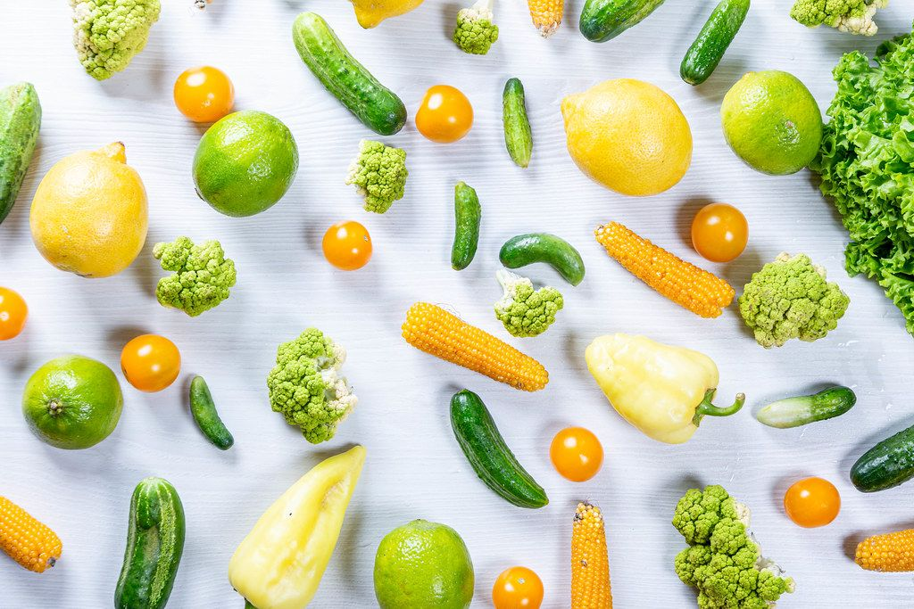 Top view fresh vegetables and fruits on white wooden background