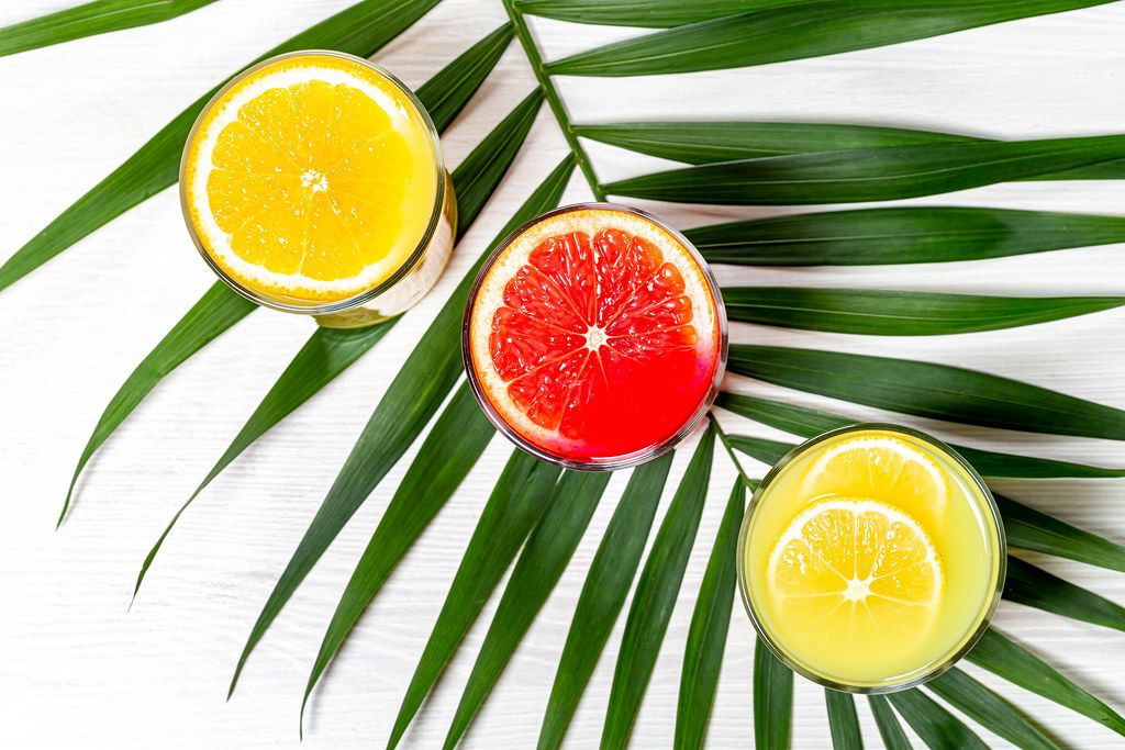 Top view glasses with lemon, orange and grapefruit juice with green leaf (Flip 2019)