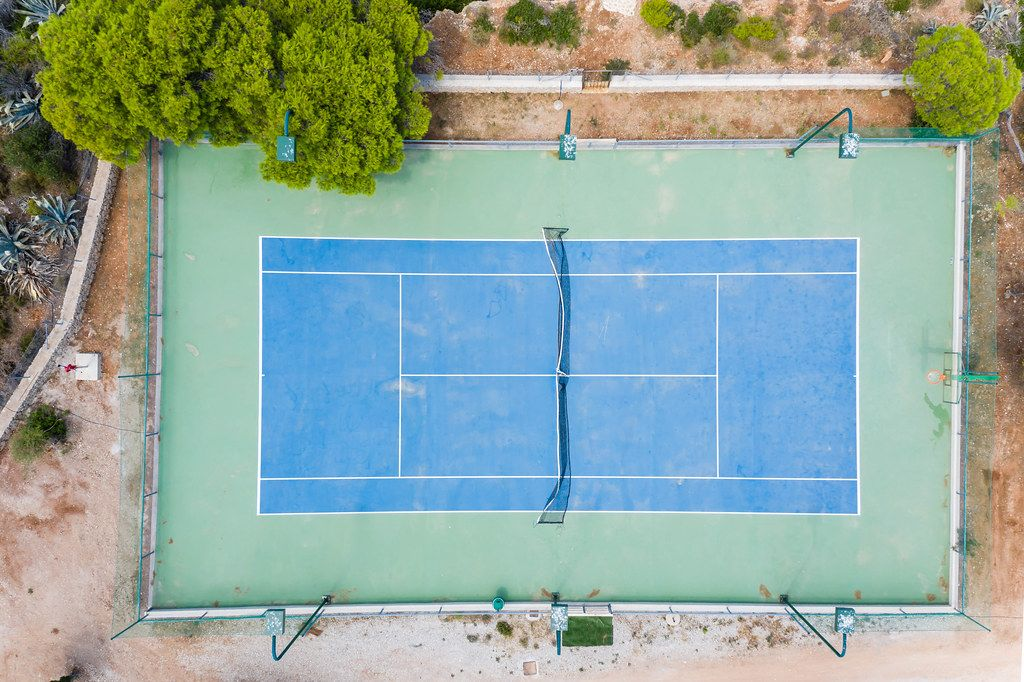 Top view of a blue and green tennis court on the greek island Spetses