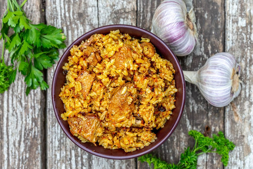 Top view of a bowl of meat pilaf on a wooden gray background with fresh parsley and garlic (Flip 2019)