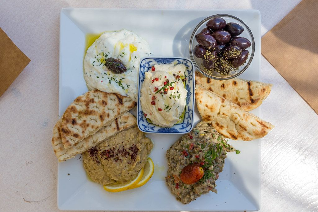 Top view of a dips Plate with pita bread, tzatziki, fresh roe dip, aubergine salad, hummus, pita bread and olives