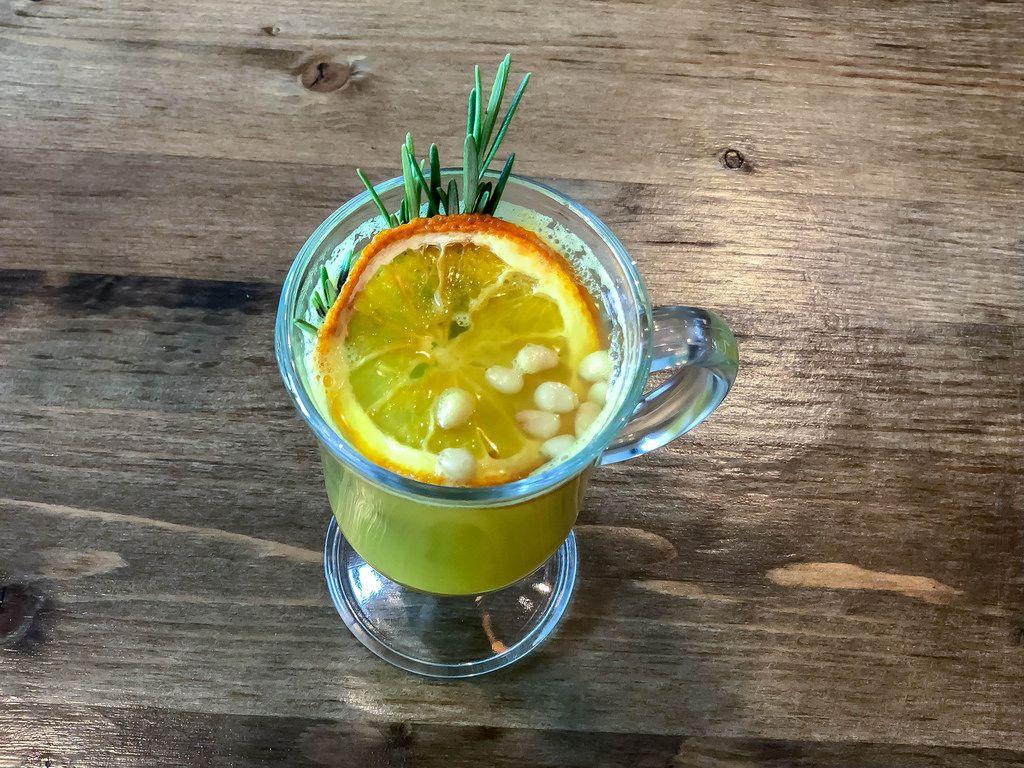 Top view of a glass of hot yoga tea with orange, ginger, honey, curcuma, pine nuts, lemon