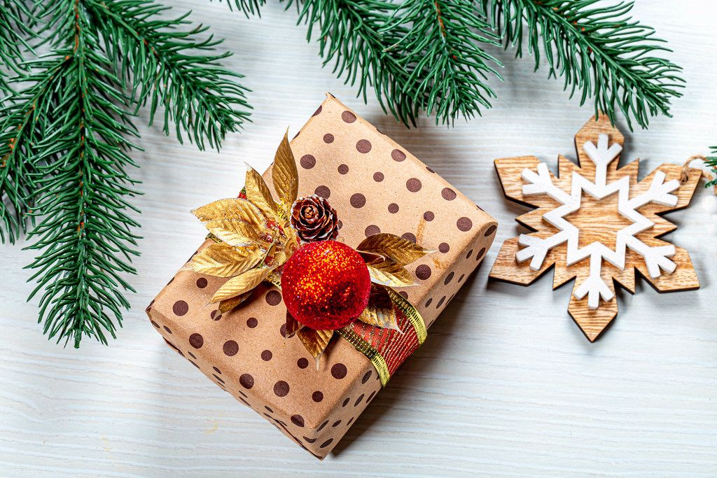 Top view of beautiful gift box and christmas tree branches on a white wooden background (Flip 2019)