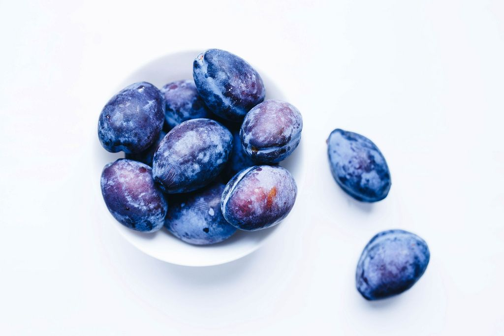 Top view of blue plums in a bowl on white background