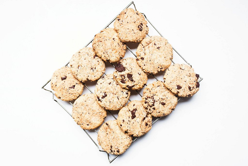 Top view of chocolate chip cookies on cooling rack i=on white background