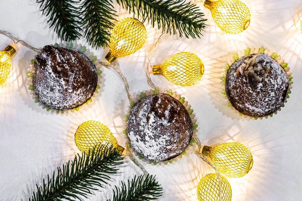 Top view of chocolate cupcakes with christmas tree branches and a luminous garland (Flip 2019)