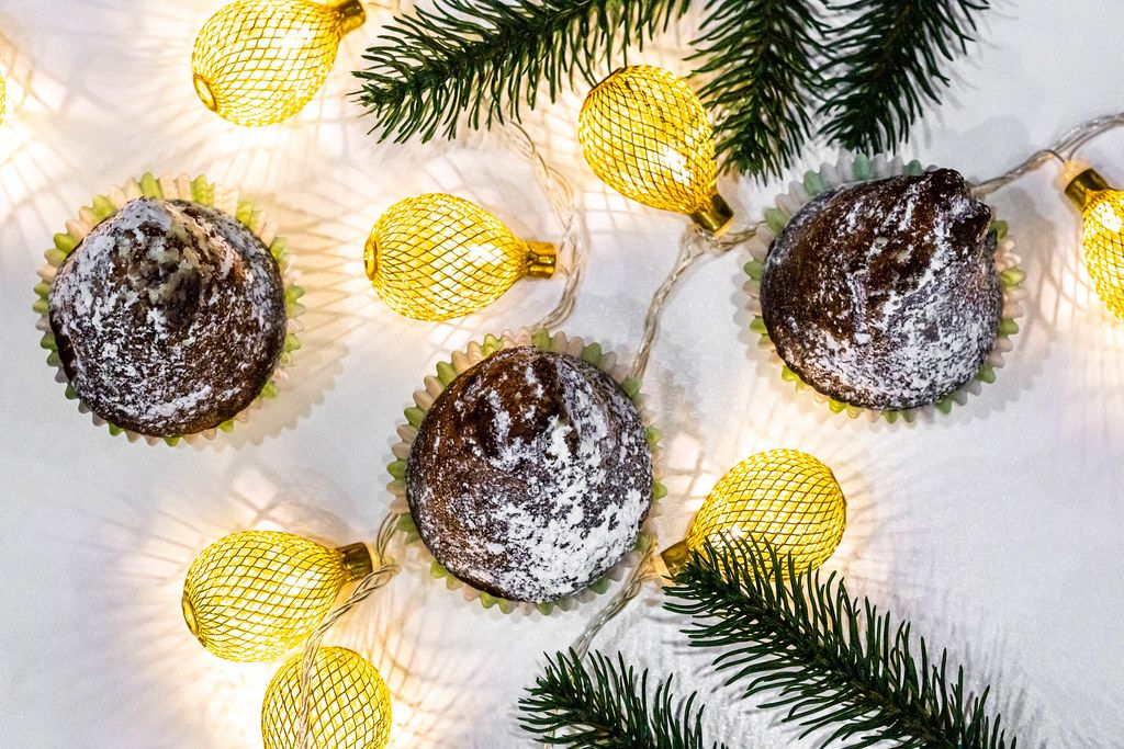 Top view of chocolate cupcakes with christmas tree branches and a luminous garland