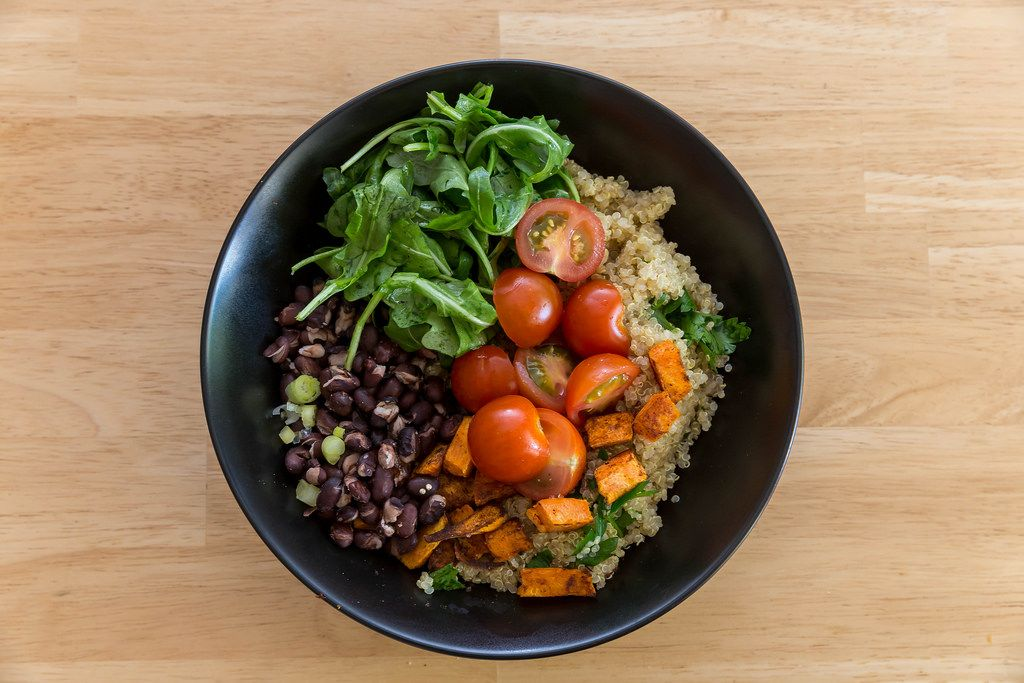 Top view of Cuban Quinoa Bowl by Hellofresh with sweet potatoes, cherry tomatoes, rocket and red beans