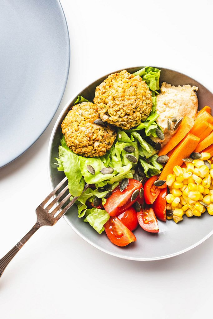 Top view of falafel buddha bowl with vegetables and hummus with fork and plate