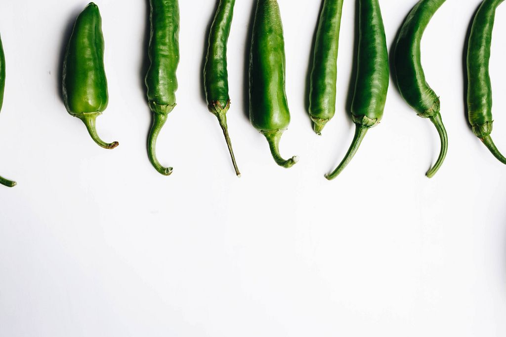 Top view of green chili peppers on white background. Details