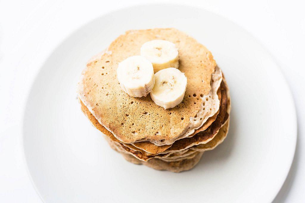 Top view of homemade vegan banana pancakes topped with banana pieces (Flip 2019) (Flip 2019) Flip 2019