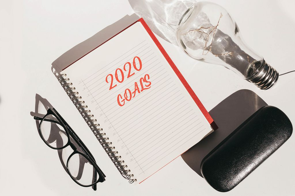 Top view of office desk with glasses and notebook with 2020 goals. New year concept.