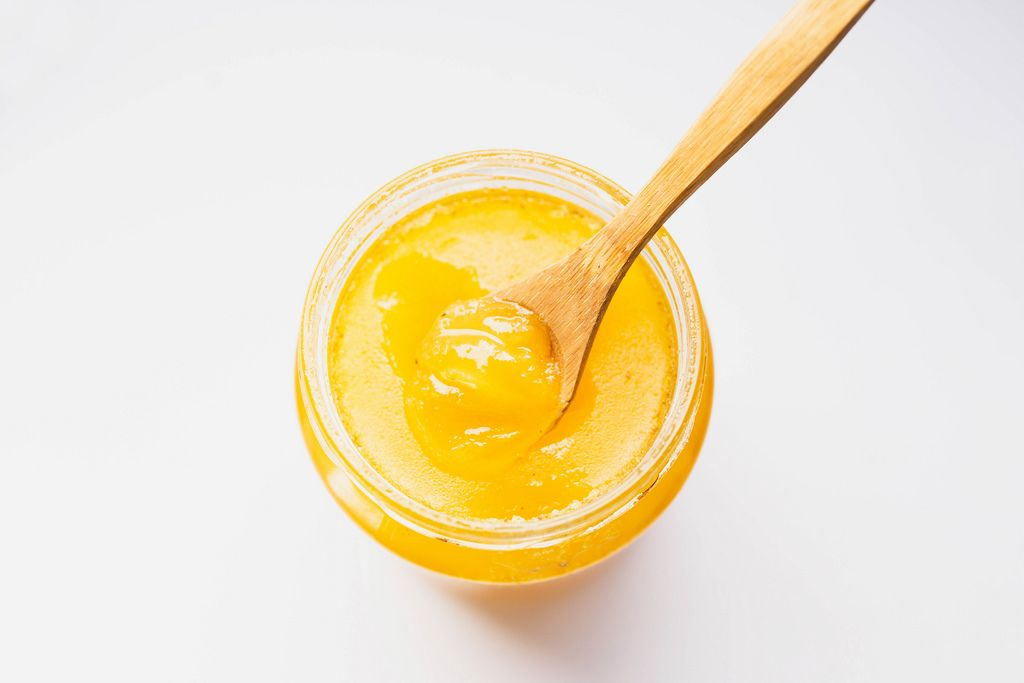 Top view of organic honey in a glass jar with wooden spoon on white background