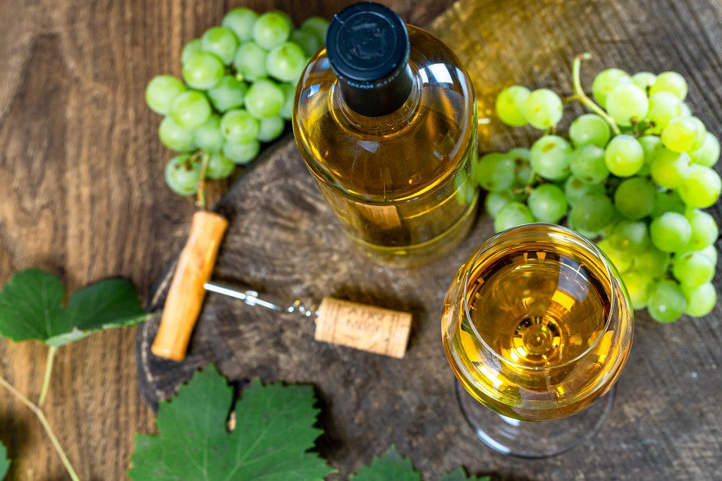 Top view of ripe grapes and white wine in bottle and glass on old wooden background (Flip 2019)