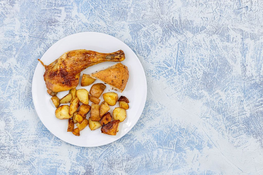 Top view of served Chicken Drumstick with Potatoes and Bread