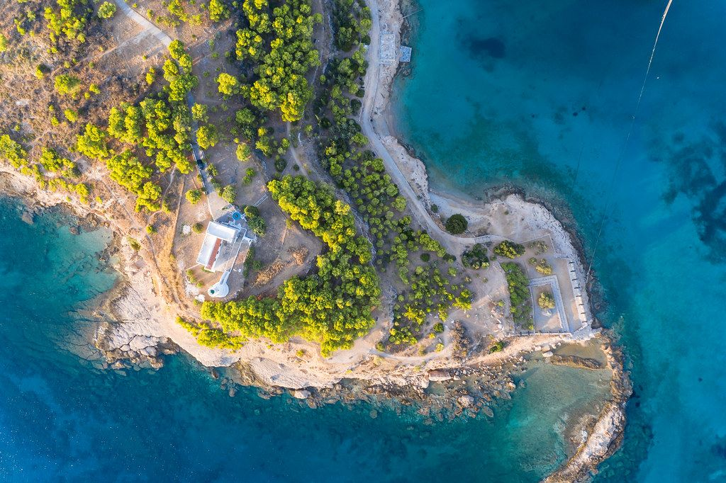 Top view of the island lighthouse of Spetses, on a rocky cliff in the blue Aegean Aea