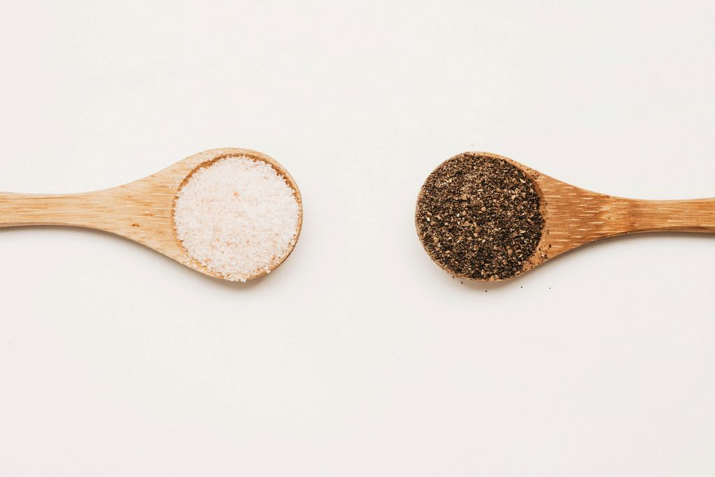 Top view of two wooden spoons with salt and pepper. White background