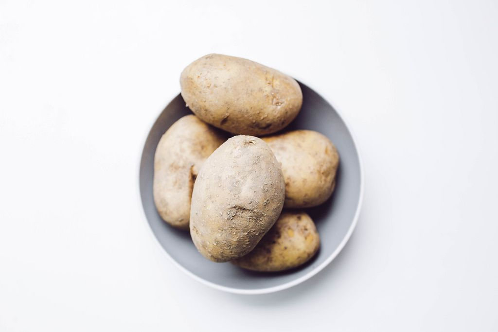 Top view of unpeeled, raw potatoes on white background