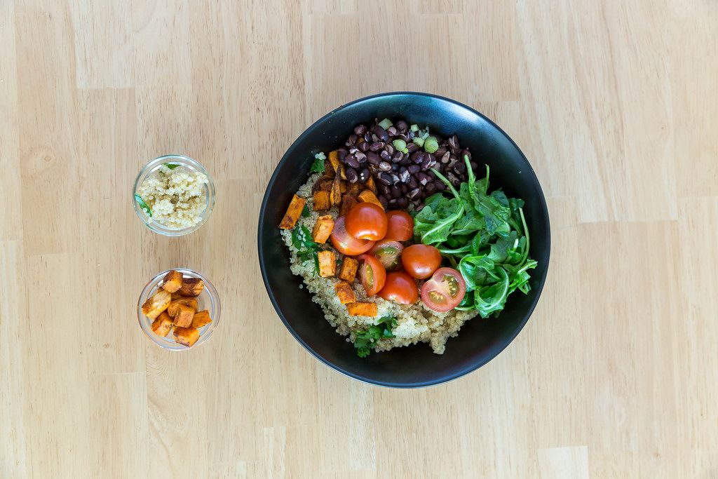 Top view of veggie bowl with sweet potatoes, cherry tomatoes, rocket and red beans