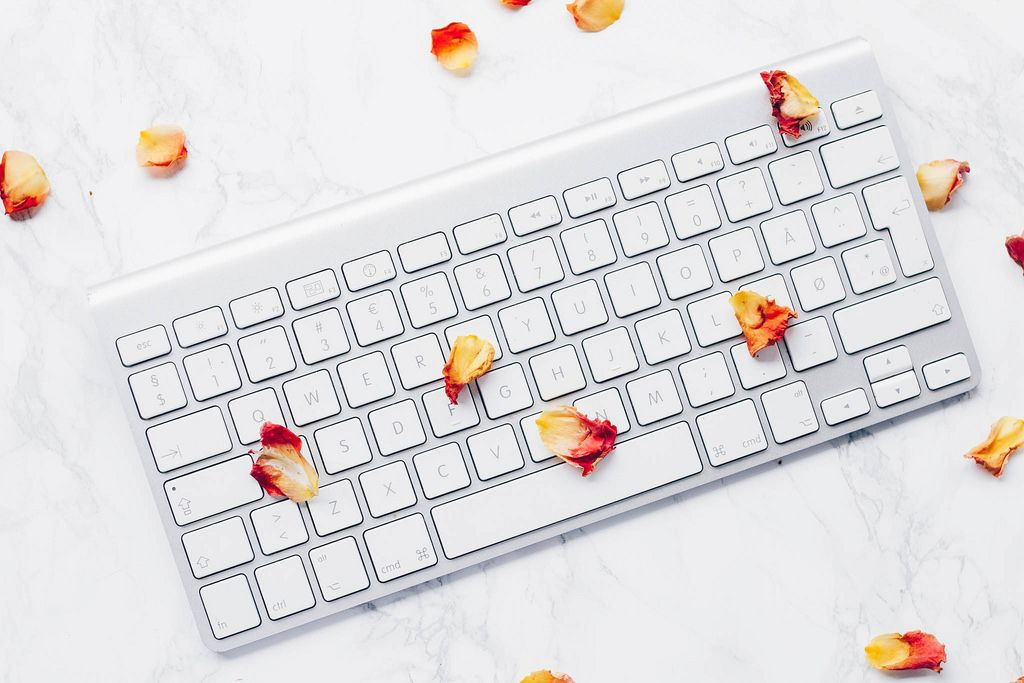 Top view of white keyboard with rose petals on marbled background