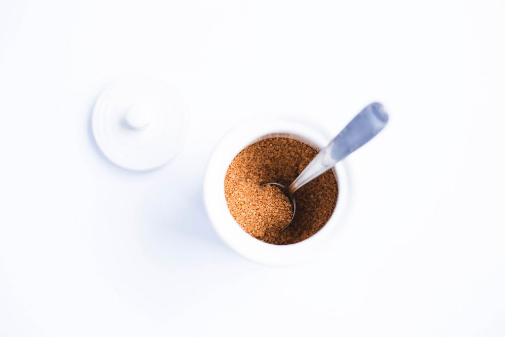 Top view of white pot of brown sugar with metal spoon on white background
