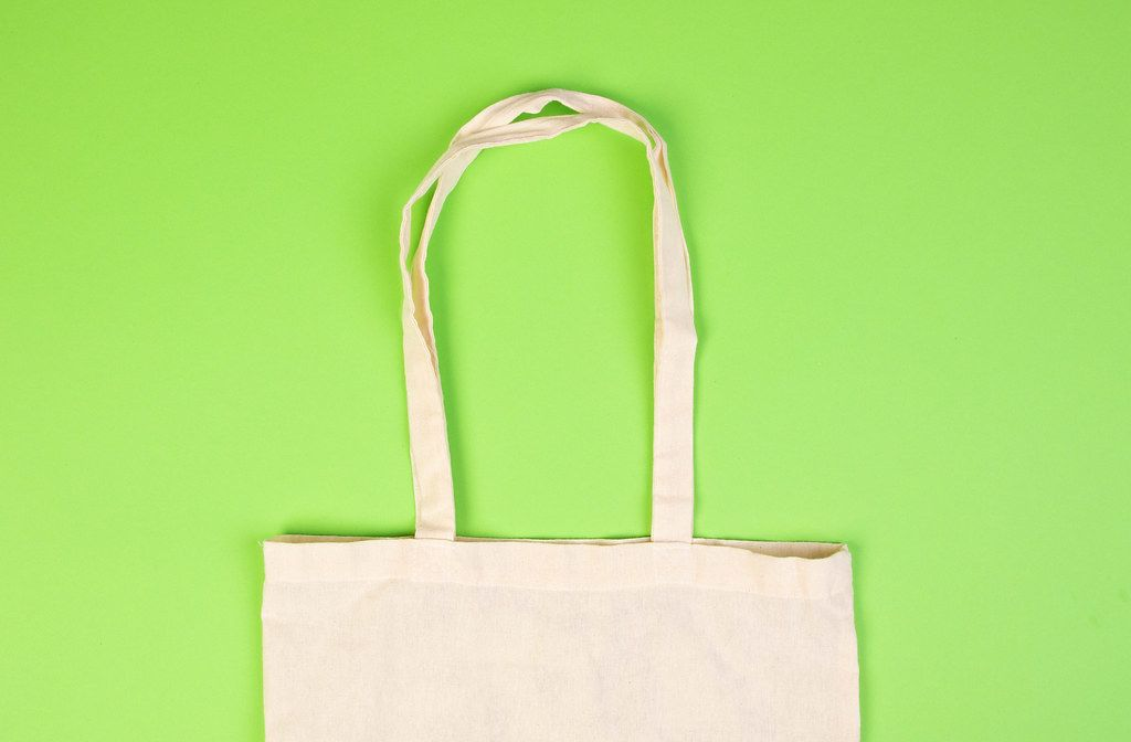 Top View Photo of reusable fabric bag on green Background