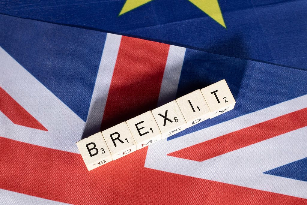 Top View Photo of Wooden Cubes forming the word Brexit on United Kingdom and European Union flags