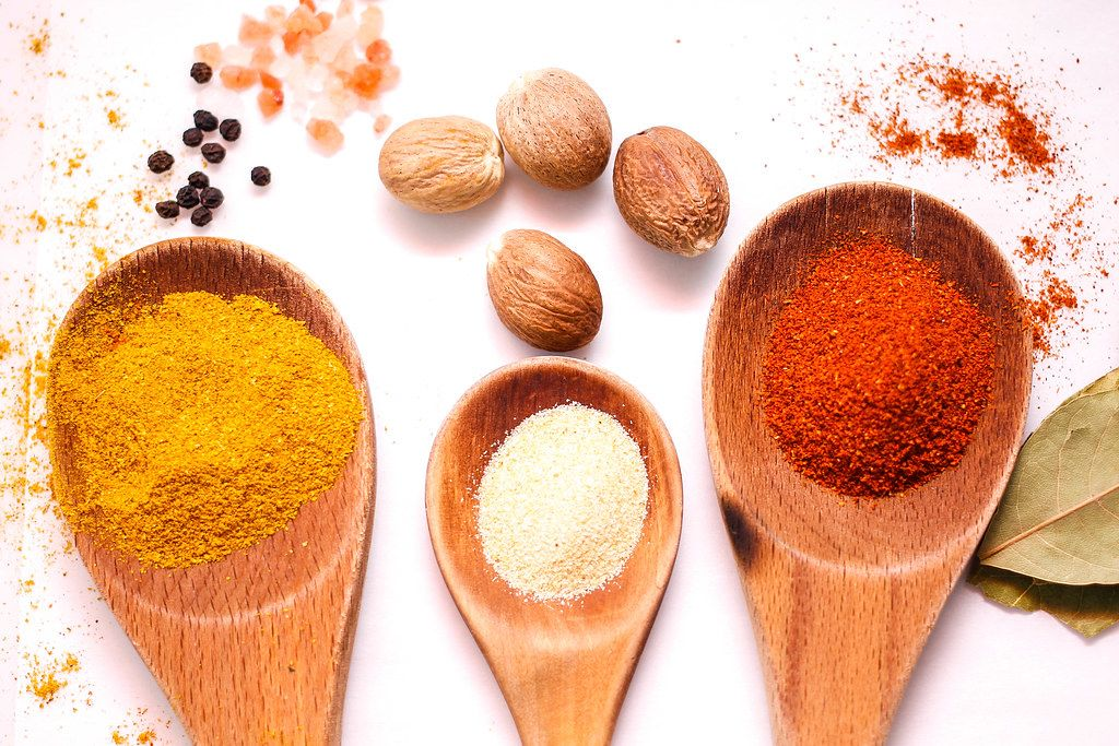 Top View Picture of Three Wooden Spoons with Chili, Curry and Garlic Spice and Walnuts